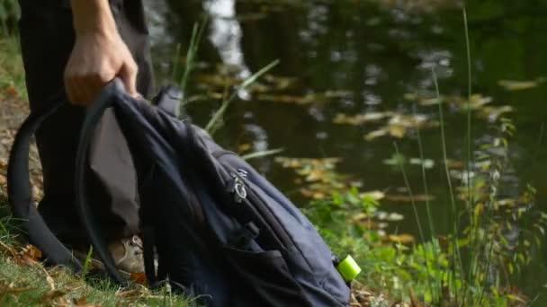 Turistické vezme a dá batoh na zem opět slunečný den parku u vody suché žluté listy plovoucí vodnaté povrchu Backpacker muž venku