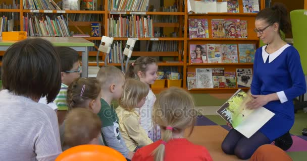 Childrens Day in Opole Educator Tells the Story to Kids in a Classroom Shows a Book to the Children Little Boy Gets up Education in Kindergarten Library