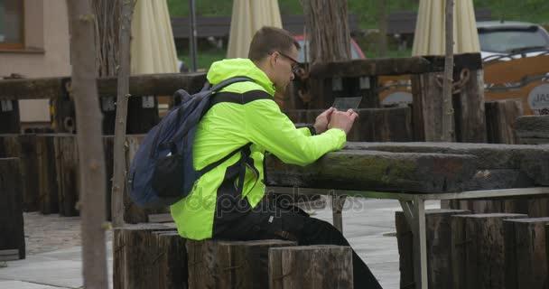 Man klickt Tablet im Cafe im freien Shopping SMS Chat Via Messenger Immobilien Kauf tun Internet Forschung junge Geschäftsmann aufsteht und Blätter