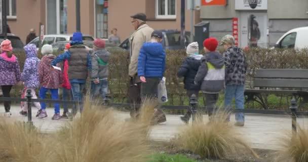 Velikonoční pondělí v Opole Polsko děti jdou vedení pedagogů učitelé děti na výlet lidí na ulici zamračený den v jarní