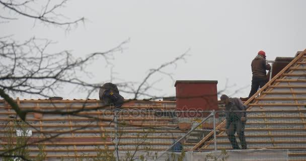Ostermontag Oppelner Dachziegel reparieren Verlegen roter Keramikziegel Arbeiter gehen oben am Gebäude Stadtbild bewölkt Tag kahle Äste Bäume