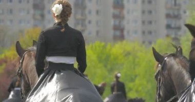 Women in Vintage Riding Clothes Riding Horses Backsides of the Riders Female Horse Regiment at Parade on the Edge of City National Holiday in Sunny Day