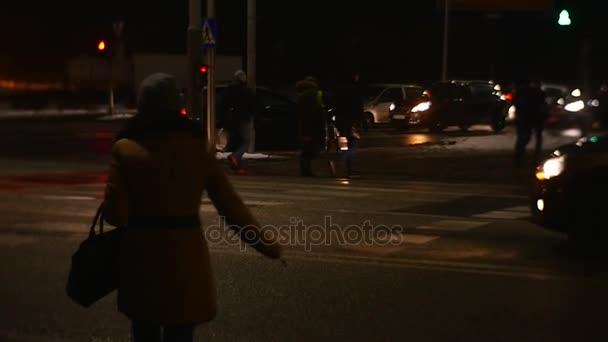 Žena vede přes silnici noční Cityscape lidí na zimní ulice pěší chůze domů ve spěchu zaneprázdněn plánu auto ustupuje světlomety sepnutém na