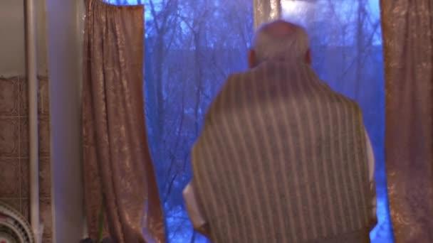 Öreg ember keresi az ablakon, türelmetlenül várakozás-re a látogatók ember már Dresed alkalommal fehér ing otthon boldog-hoz üdvözöl a vendégek