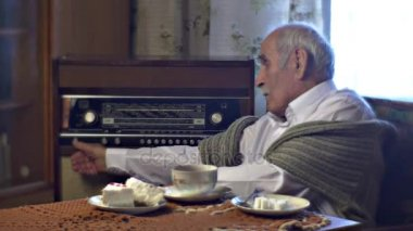 Grandad Setting Radiogram in Lunch Time Tea Cup Cake Piece on the Table in Cosy Living Room Cold Wintry Day at Home Vintage Interior Comfortable Armchair