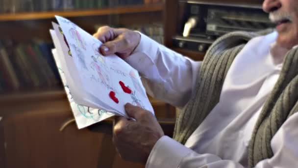 Starší muž ukazuje dětské kresby velká rodina dědeček je obklopen tím Sweet Memories Vintage interiéru z člověka domu teplé útulné místnosti šťastný starý muž