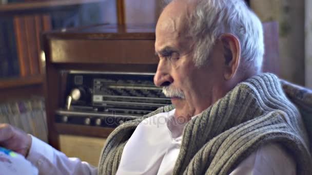 Starý muž dědeček se dívá na dětské kresby čekání pro jeho vnoučata si návštěvu rodiny sešli společně na dědečka místo Vintage interiéru