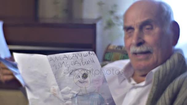 Starší člověk je rád, že obdrží dárek od dětí hospodářství kresby a ukazuje, že je hrdý na jeho Happy velká rodina dědeček není osamělý v útulné místnosti