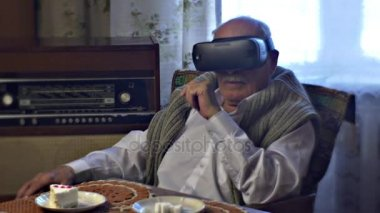 Old Man Seems Disappointed With vr Glasses Pointing to Something Playing Game Takes the Headset Off Sitting at the Table Covered With Knitted Tablecloth