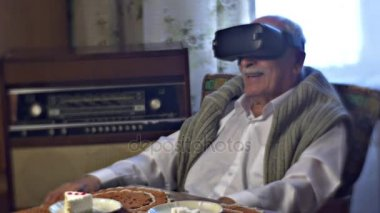Grandfather in vr Goggles Describes What he Sees Watching Amazing Video and Wondering Link of Times Old Furniture Quiet Place Piece of Cake on a Table