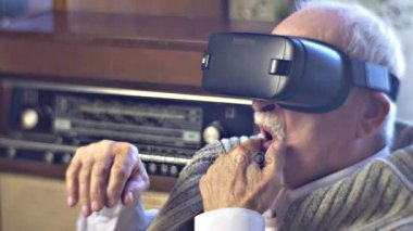 Man Wipes His Mustache Turning Head in vr Headset Watching Video and Wondering Obsolete Radiogram is on a Background Link of Times Man Chooses Modern Device