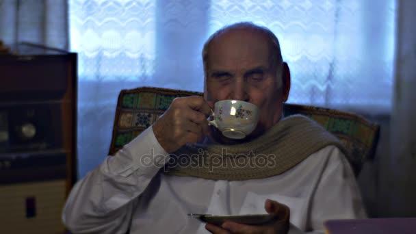 Spokojený starý člověk je pití čaje a Talking sedí u stolu v křesle v útulné obývací pokoj rodiny Holiday chladný zimní den doma Vintage interiéru