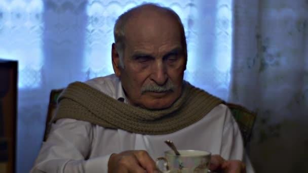 Starý dědeček dá šátek na jedné a cukřením čajové posezení v útulné obývací pokoj chladný zimní den víkendu na domácí Vintage interiéru a krásné poháry Radiogram
