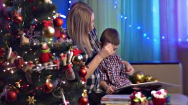 Young Mother is Reading Books With Her Son Family Celebrates Christmas Decorated New Year Tree Pregnant Mom and Little Boy Are Waiting For Baby Cosy Room