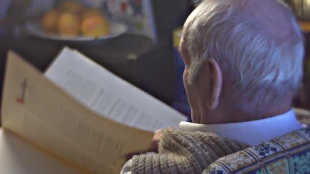 Starší lékař vědec, hledá prostřednictvím knihy následuje Text s prstem pozorně studovat materiál vzpomínky starého muže Vintage interiéru