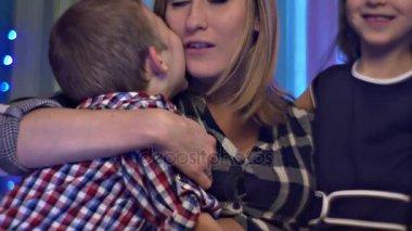 Šťastná maminka objetí líbá jeho syn a dcera něžně rodina slaví vánoční svátky v domácí Těhotná maminka a dvě její děti růží z textilie