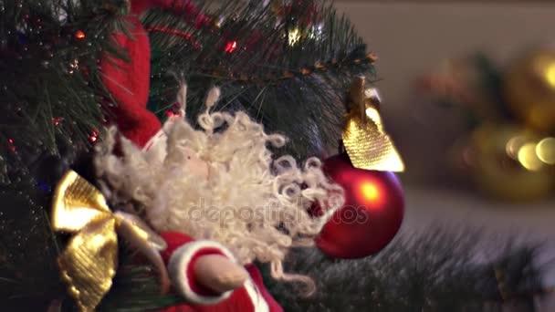 Plüsch-Weihnachtsmann hängt am grünen Weihnachtsbaum