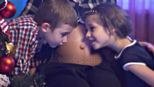 Dojemné scény děti cítí dítě kope do břicha podporuje řada těhotná matka dvě její děti čekají dítě bratr sestru zdravé těhotenství