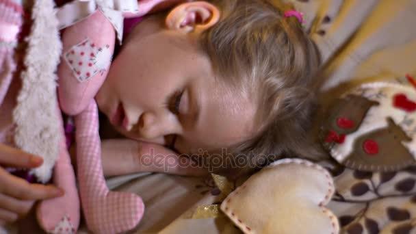 Aranyos gyerek is alszik a neki kéz alatt fej lány ölelést ő szeretett puha játékok nyúl medve úgy érezte, szarvast szív dekoratív játékok édes otthon játékos kisgyerek