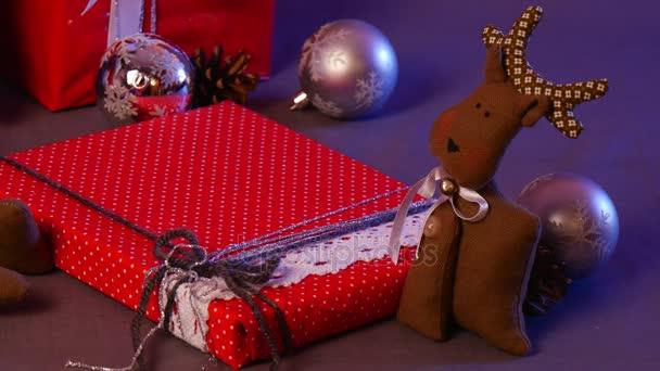 Kézzel készített karácsonyi játékok vannak alatt egy fenyő, beleértve egy vicces szarvas, foltos szív, két doboz a karácsonyi ajándékok és így tovább