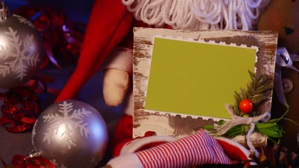 Ruce muže vzít a slavnostní ruku z kapsy s kartami prezentace pod dekorovaný vánoční strom jedle, se spoustou šumivé koule