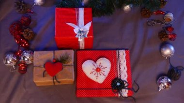 Man`s Hands Put a Festive Hand Made White Heart and a Pack With Slide Show Cards, Under a Decorated Christmas Fir Tree, With a Lot of Sparkling Balls