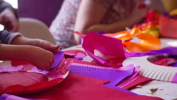 Dospělé a jejich děti aby pěkné srdce z barevného papíru přilepit dolů bílé kulaté plastové polotovary k oslavě svatého Valentýna v pomalém pohybu