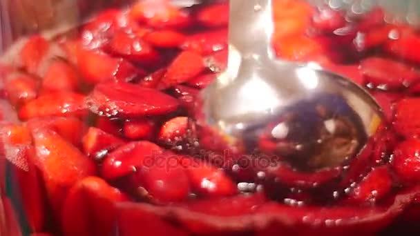 Das Barkeeper gießt eine Erdbeere kalten Erfrischungsgetränk mit einer Metall-Kugel aus Glas großer Kapazität. Sommer-Erdbeer-Party, Ihren Durst