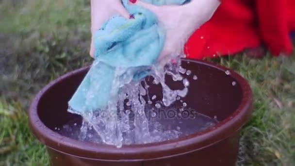 Dunkelhaarige Frau ist mit Wäschewaschen beschäftigt