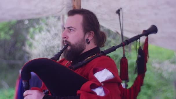 Long-Haired Bearded Man is Playing on Bagpipes