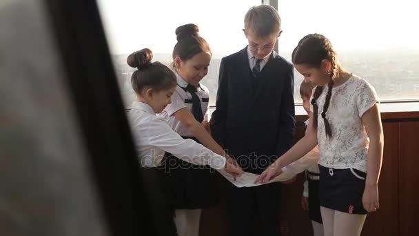 Business children look topographic map near the window