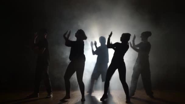 Pět tanečníků tančí synchronně v kouři