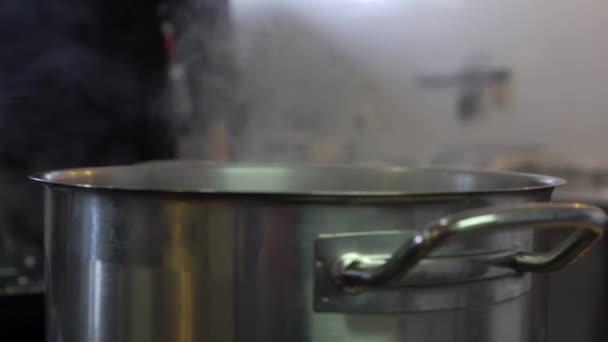 Voda vaří v hliníku kastrol na elektrický sporák v restauraci