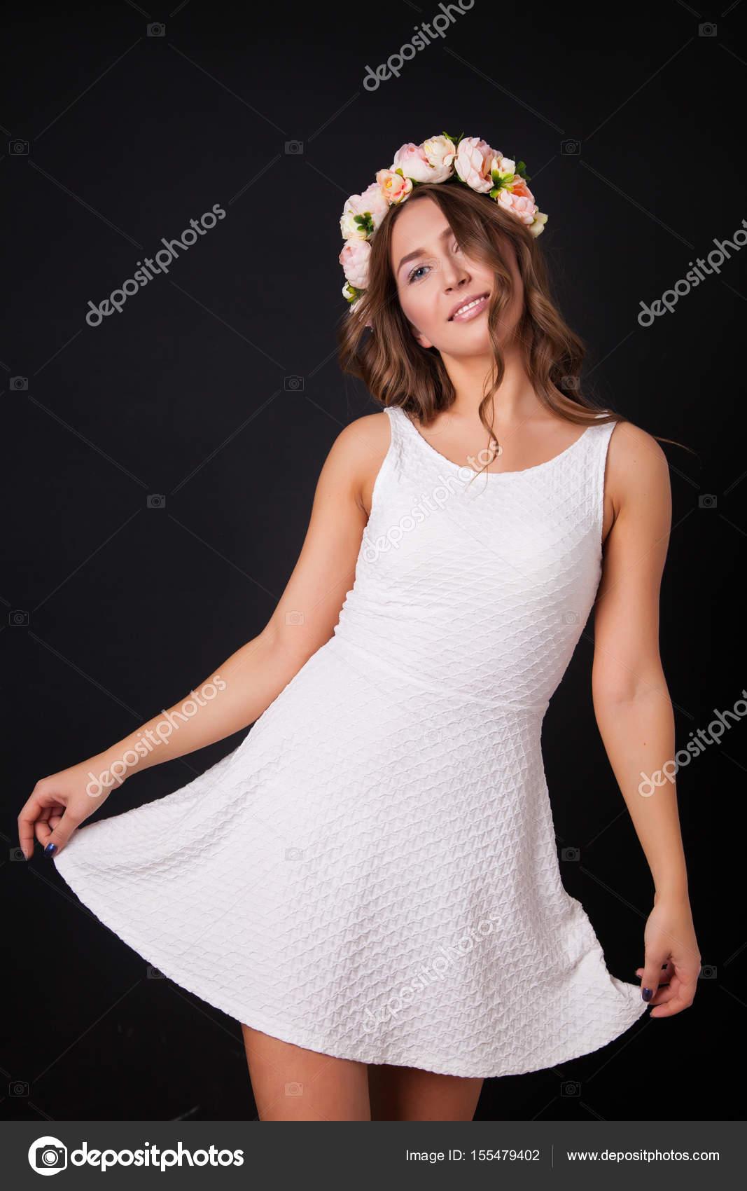 Schöne Mädchen in einem weißen Kleid mit Blumen auf dem Kopf auf ...