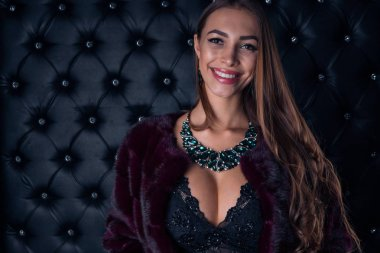 Luxurious young beautiful girl with beautiful adornments smiling at the camera on a dark background