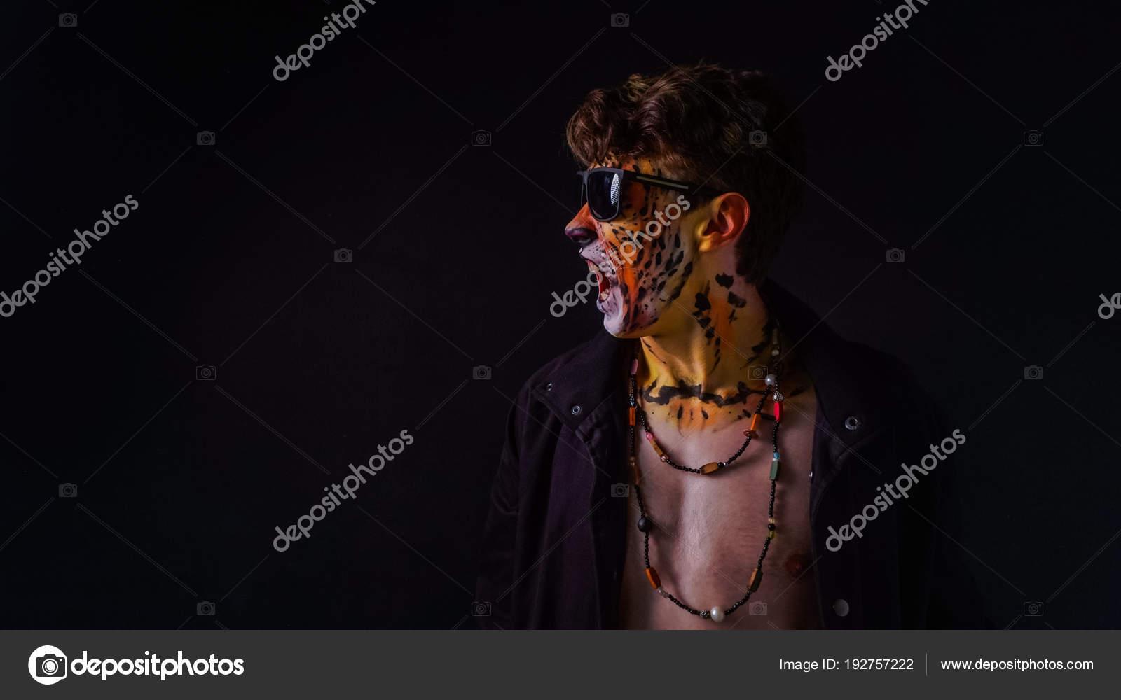 Un chico con un tigre en su rostro con gafas de sol sobre un fondo ...