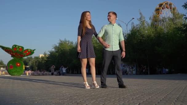 Fiatal pár sétál a parkban. Naplemente.