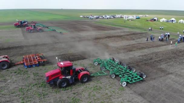 Vörös traktor a mezőn szántja a földet.