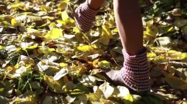 A girl in boots walking on a sunny autumn road, covered with fallen leaves