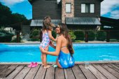 Fotografie mother and daughter near pool