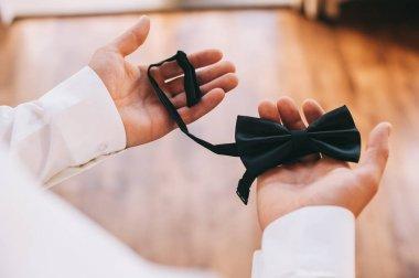 groom holding bow tie