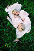 Fotografie sisters twins lying on grass