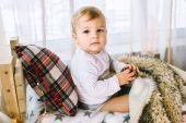 Fotografie kleiner Junge hält Tannenzapfen