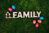 Fotografie Holzbuchstaben Familie und Ostereier auf dem grünen Rasen