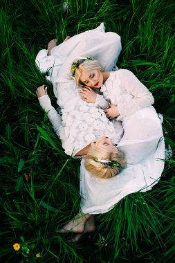 two attractive twin sisters lying on green grass