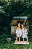 Photo two beautiful girls in antique shirts near a well
