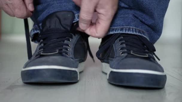 Mann, der sich auf einen Spaziergang vorbereitet und die Schnürsenkel an seine Sportschuhe bindet