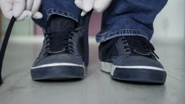 Mann bereitet sich auf Spaziergang vor und bindet Schnürsenkel mit Schutzhandschuhen an Sportschuhe