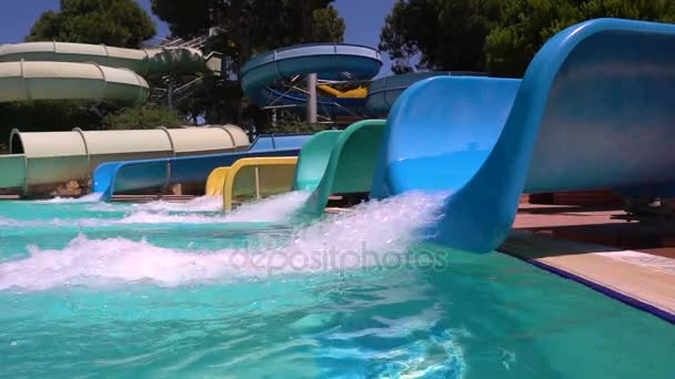 Man descends from water slide. The guy is smiling at camera. Aquapark. Slow motion.