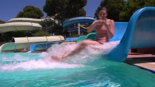 Woman descends from water slide. The girl is smiling at camera. Aquapark. Slow motion.